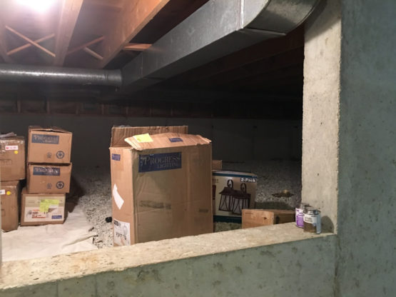 a damp crawl space in a Naperville, IL home full of boxes before crawl space encapsulation
