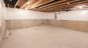 A clean, unfinished basement has been waterproofed.